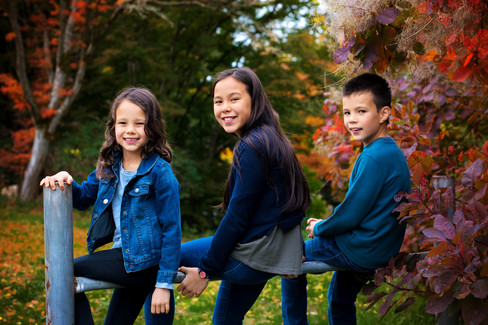 Three children sitting on a post in Queen Elizabeth Park by Vancouver family photographer Amber Theresa Photography.