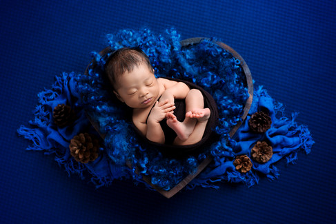 Newborn baby boy in royal blue in a a wooden heart shape prop by Vancouver newborn photographer Amber Theresa Photography