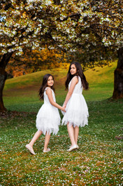 Young sisters in white pixie dresses holding hands and looking over their shoulders in the cherry blossoms at Queen Elizabeth Park in Vancouver.