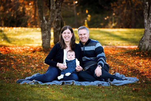 Mother, father and infant sitting in the fall leaves on a blanket at Queen Elizabeth Park in Vancouver.