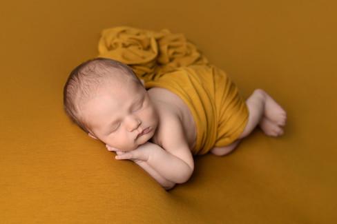 Newborn baby boy in mustard yellow posed with prayer hands.