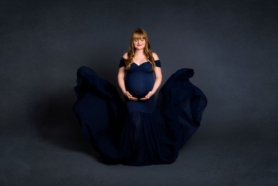 Pregnant woman in a navy blue maternity gown holding her belly with the dress tossed behind her in studio | Maternity Photographer Vancouver | Amber Theresa Photography