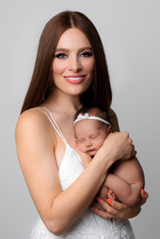 Beautiful mother Chloé Morgan holding her new baby girl by newborn photographer Amber Theresa Photography