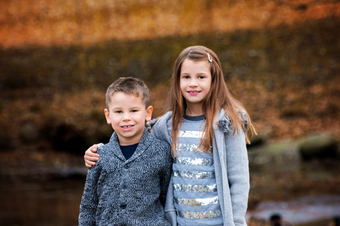 Brother and sister hugging and smiling in front of the duck pond at Queen Elizabeth Park in Vancouver