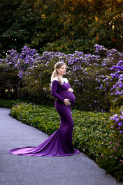 Pregnant woman wearing a long sleeve grape purple maternity gown standing on a path surrounded by purple flowers at Deer Lake Park in Burnaby | Maternity Photographer Vancouver | Amber Theresa Photography