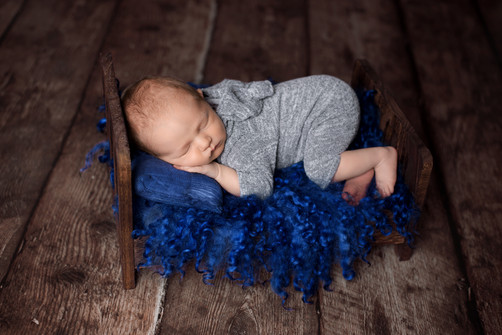Newborn baby boy in a bear hat grey romper in bum-up pose on curly blue wool in a brown wooden bed.