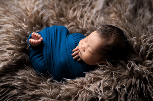 Newborn baby boy in teal criss cross wrap with toes peeking out on a brown flokati rug by Vancouver newborn photographer Amber Theresa Photography