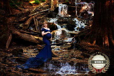 Pregnant woman wearing a cap sleeve navy blue maternity gown standing in the river at Bridal Veil Falls in Chilliwack | Maternity Photographer Vancouver | Amber Theresa Photography