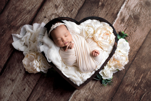 Newborn baby girl in cream and white posed in a wooden heart prop by Vancouver newborn photographer Amber Theresa Photography