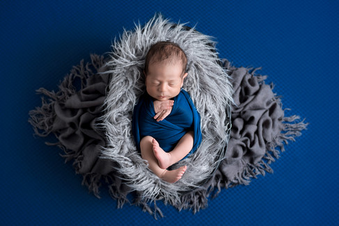Newborn baby boy in a dark teal wrap laying in a grey fur basket by Vancouver newborn photographer Amber Theresa Photography