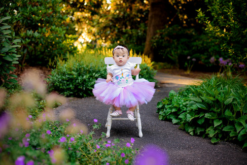12 month baby girl in a pink tutu on a chair in a path surrounded by purple flowers at Deer Lake Park in Burnaby.