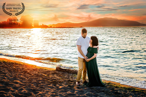 Expectant mother wearing a ruffle top forest green maternity gown smiling at husband at Jericho Beach during sunset | Maternity Photographer Vancouver | Amber Theresa Photography