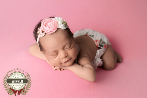 Newborn baby girl wearing a pink floral romper smiling with hands under chin on pink white blanket.