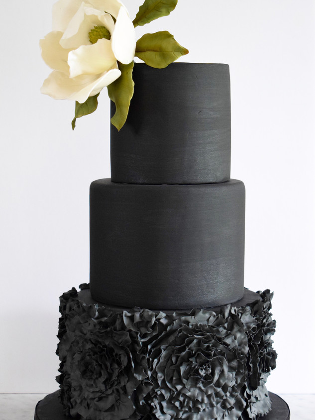 Black wedding cake with sugar magnolia and ruffles