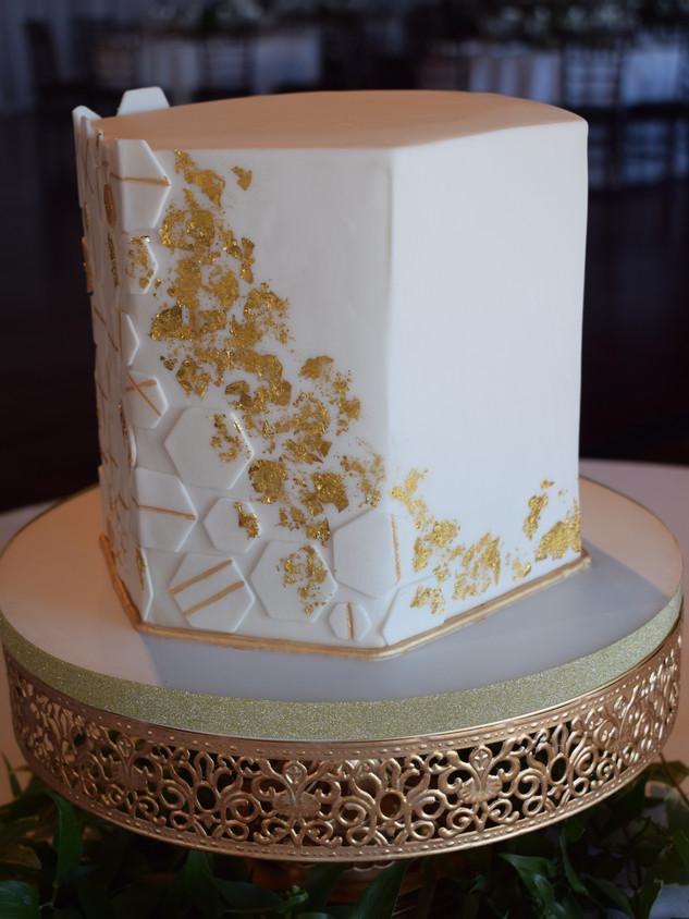 Modern hexagon cake with geometric gold tiles