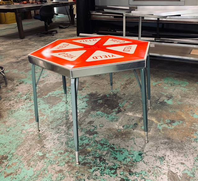 Yield sign table, reclaimed table legs and scrap metal