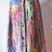 Front of cape embroidered with hand drawn digitally embroidered feathers, paint and glass beads.