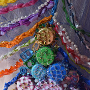 Close up of the skirt embroidery - crochet plastic bags, ring pulls, bottletops, fishnets and crystal beads.