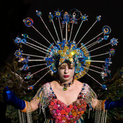 A headpiece with lights created from bottletops, knitting needles, plastic bags, tights, Swarovski crystals, broken jewellery, ring pulls and semi-precious stones. Photo by Alla Sanders.