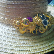 A plain straw hat embellished with vintage buttons for a client.