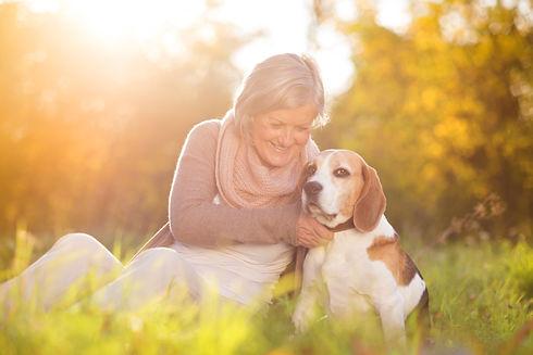 Senior woman hugs her beagle dog in coun