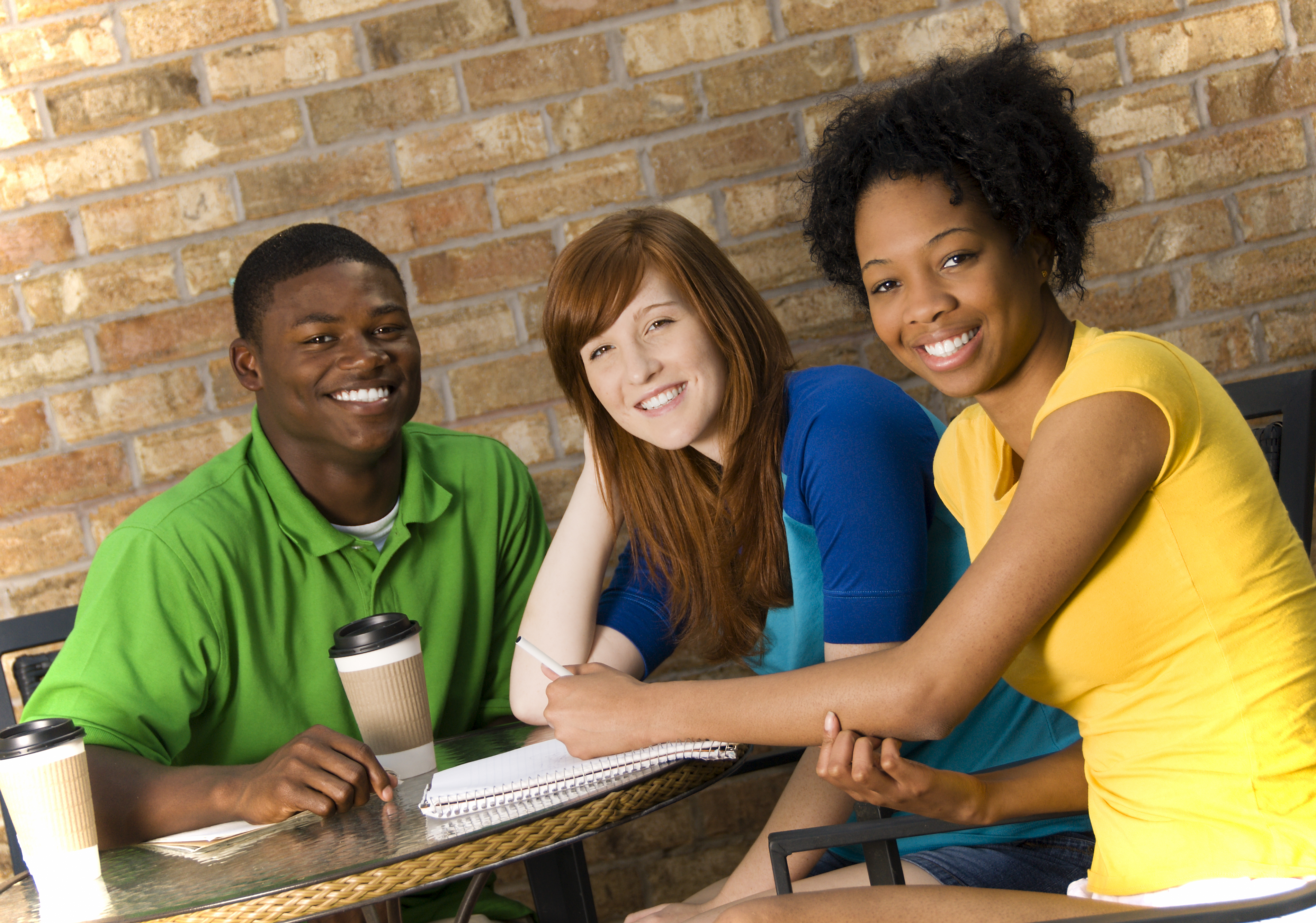 three smiling college aged students