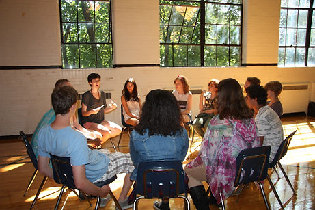 students sitting in circle in sunlit gym having a student-led discussion