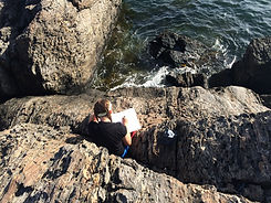 student writing poetry on the rocks by the ocean
