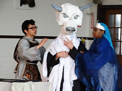 Students performing a play with costumes and puppetry
