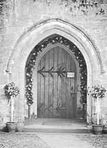Church door entrance with flower arch and topiary trees