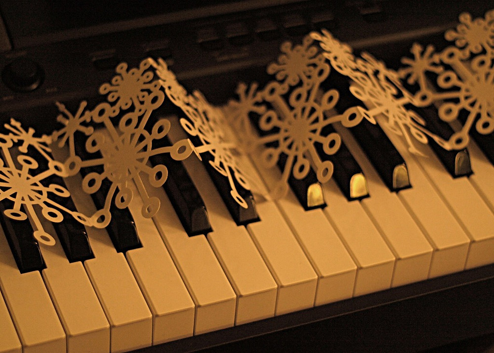 Paper snowflakes on top of piano keys