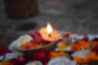 a candle burning on red, orange and white flowers