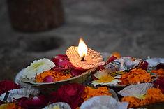 Brennende Kerze auf bunten Blumenblätter, Symbol Trauer