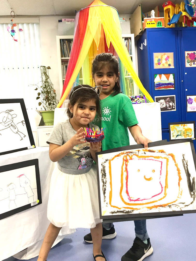 A Geneva student and her sister, an alum, pose with a masterpiece.