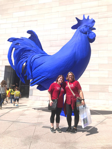"Kindergarten teachers, Mrs. Hepburn and Ms. Lieberman, pose by the National Gallery of Art's Blue Hen statue. Might we say that everything they do is a ""feather in the cap"" of our extraordinary programming?"