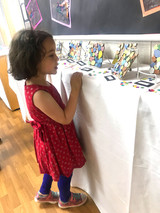 Up close, this student examines tile mosaics by Kindergarten artists.