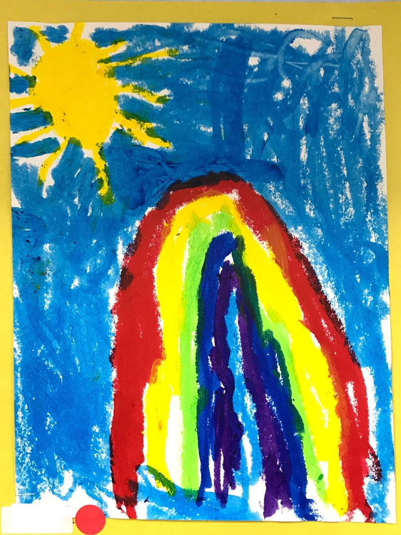 Rainbow and sun beam from a vividly blue sky.