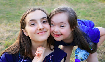 Young girl with down syndrome with older sister.