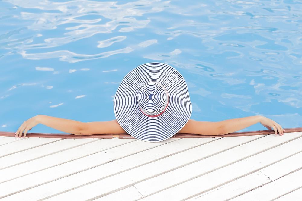 woman in hat relaxing in swimming pool