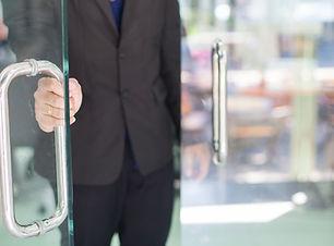 Man's hand open the door with glass refl