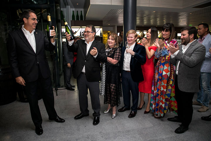 Eduardo Negron y Rafael Gavilanes junto a su familia descorchan botella de champán para celebrar la apertura de Tinto y Blanco.