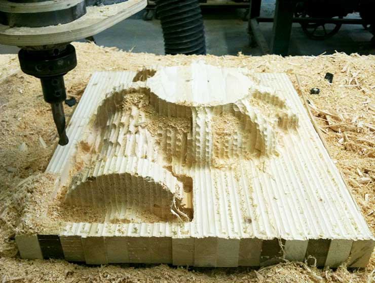 CNC machining a wood pattern of an inlet casting for the gas production industry.
