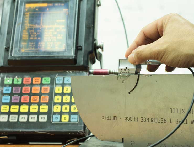 Calibrating for an ultrasonic inspection of various stainless steel parts.