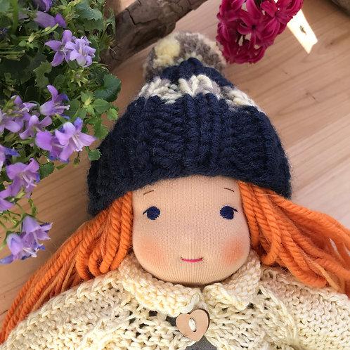 Рыжая девочка в синей шапке с помпоном