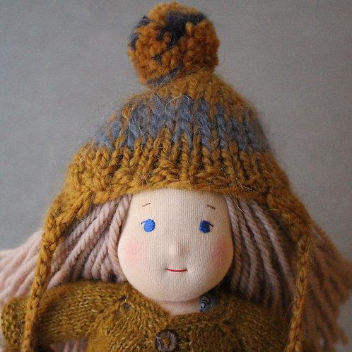 Русая девочка в горчичной шапке с помпонами.