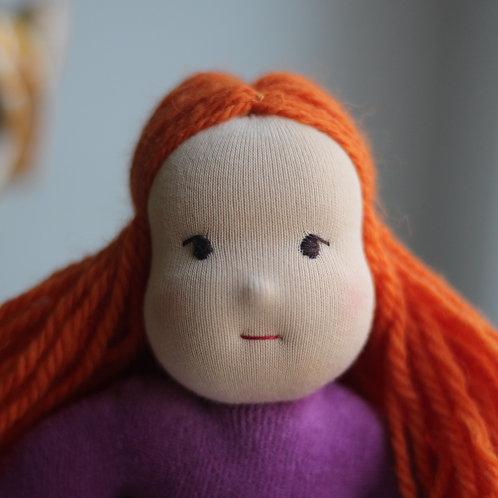 Рыжая девочка в фиолетовом костюме.