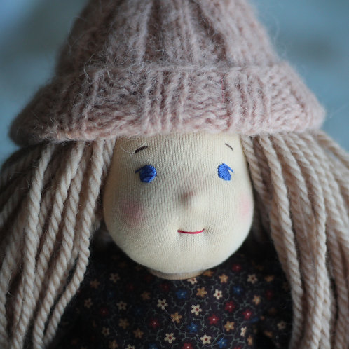 Русая девочка в розовой шапке.