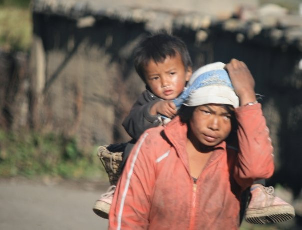 A mother carries her son up the mountain in a basket Mustang, Nepal