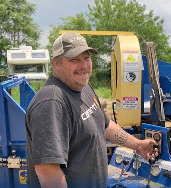 Picture of Chris Miller in front of one of his wood cutting machines.