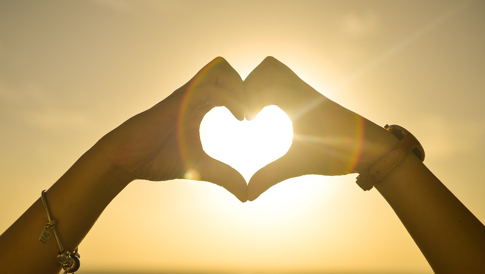 Picture of two hands creating a heart shape with sunset in background.